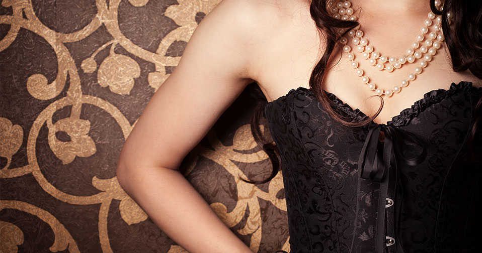 Woman wearing black corset showing off bare arms against fancy wallpaper.
