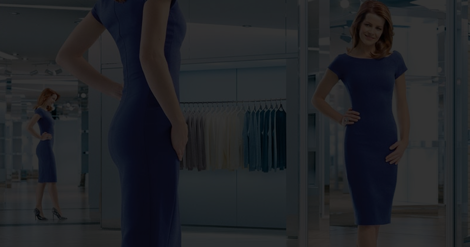 Woman wearing blue dress looking at herself in mirror