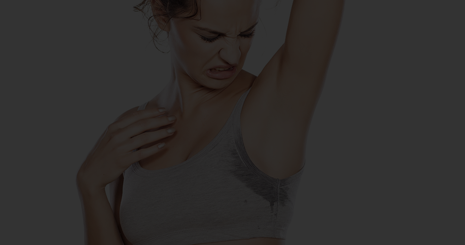 Woman looking at her sweaty armpit.