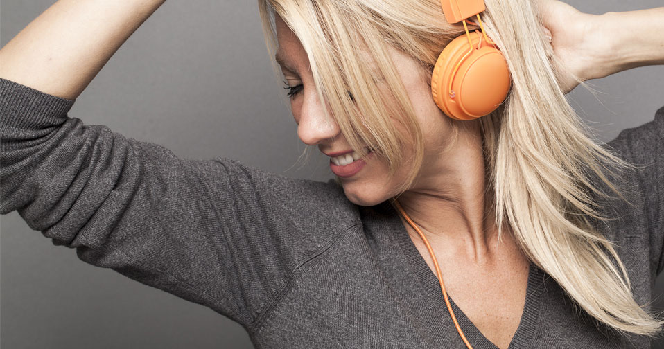 Woman with blonde hair listening to earphones and smiling.