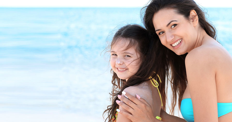 Woman in bathing suit with daughter at beach.