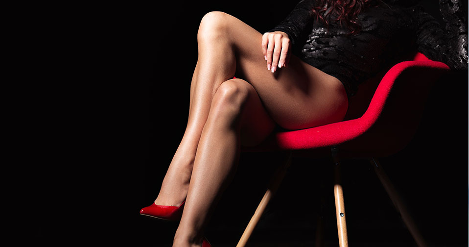 Woman's lean legs in black stilettos sitting on armchair.