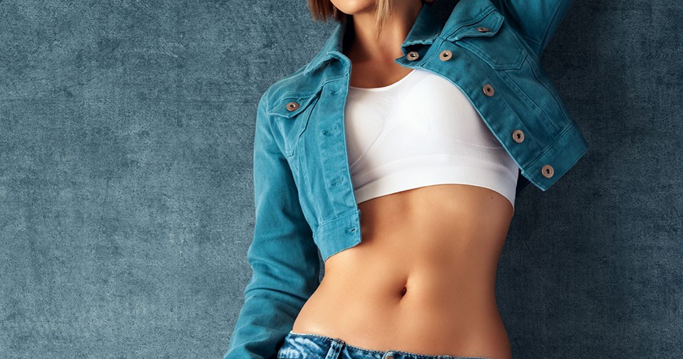 Woman wearing tight cropped shirt showing off lean stomach after tummy tuck.