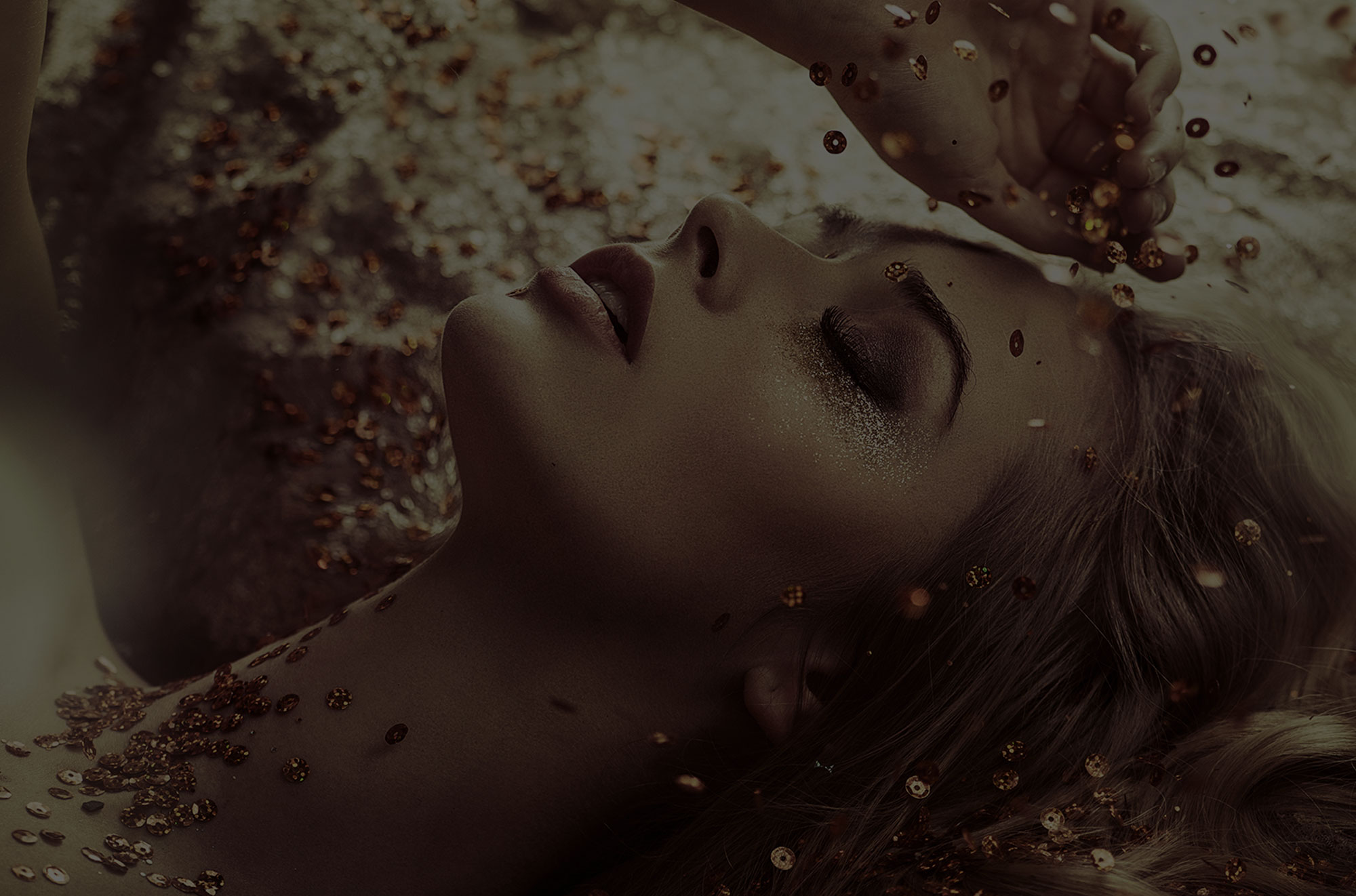 Blonde woman lying back as gold sequins fall on her on gold background.