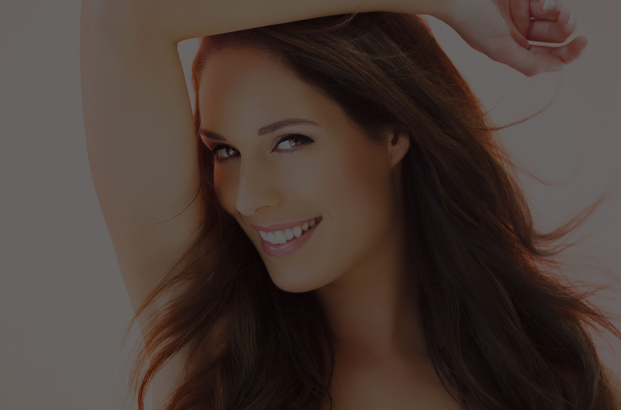 Woman with long brown hair and arm up to her head smiling and showing smooth forehead after brow lift.
