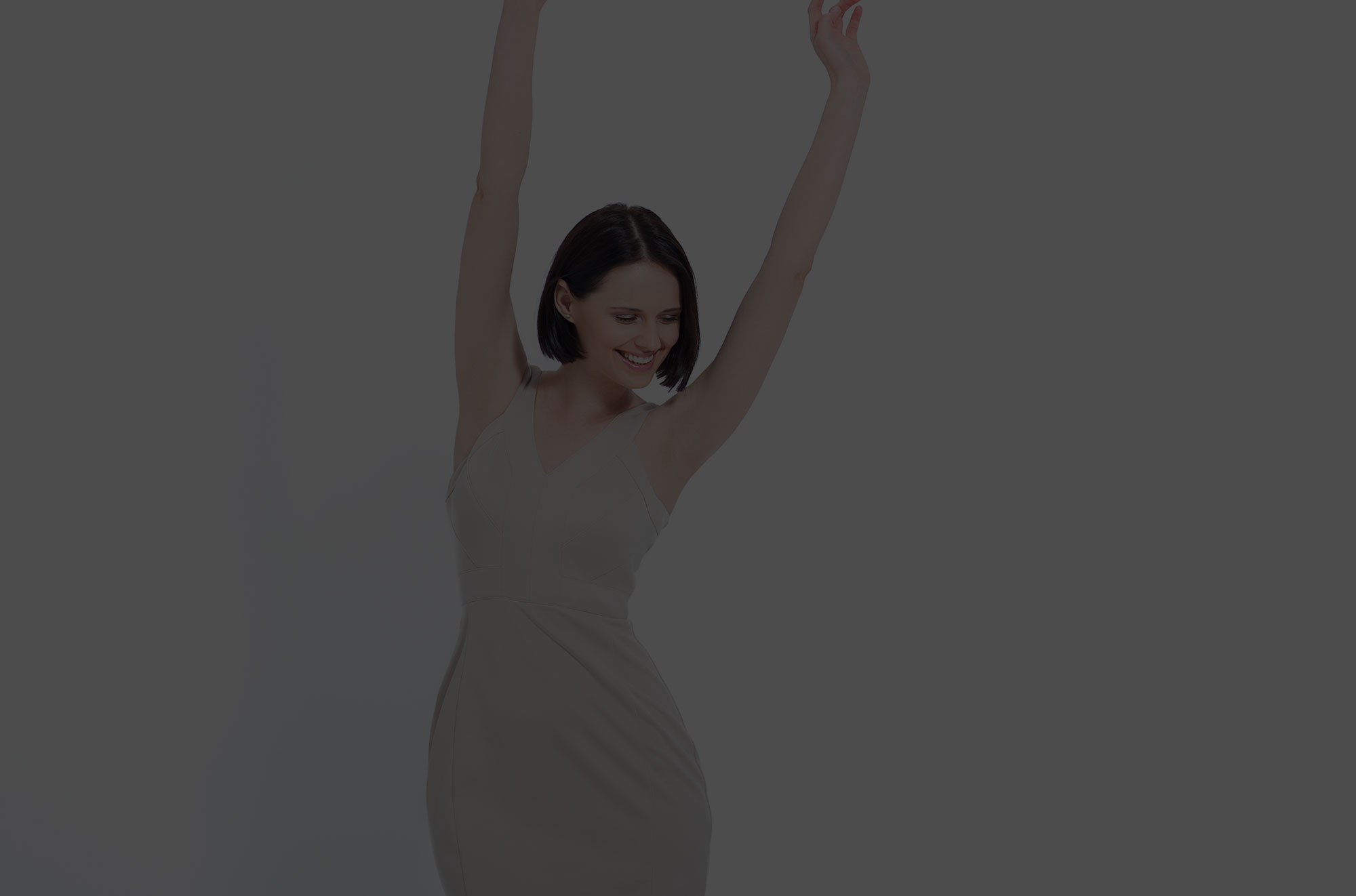 Woman smiling with hands up in the air.