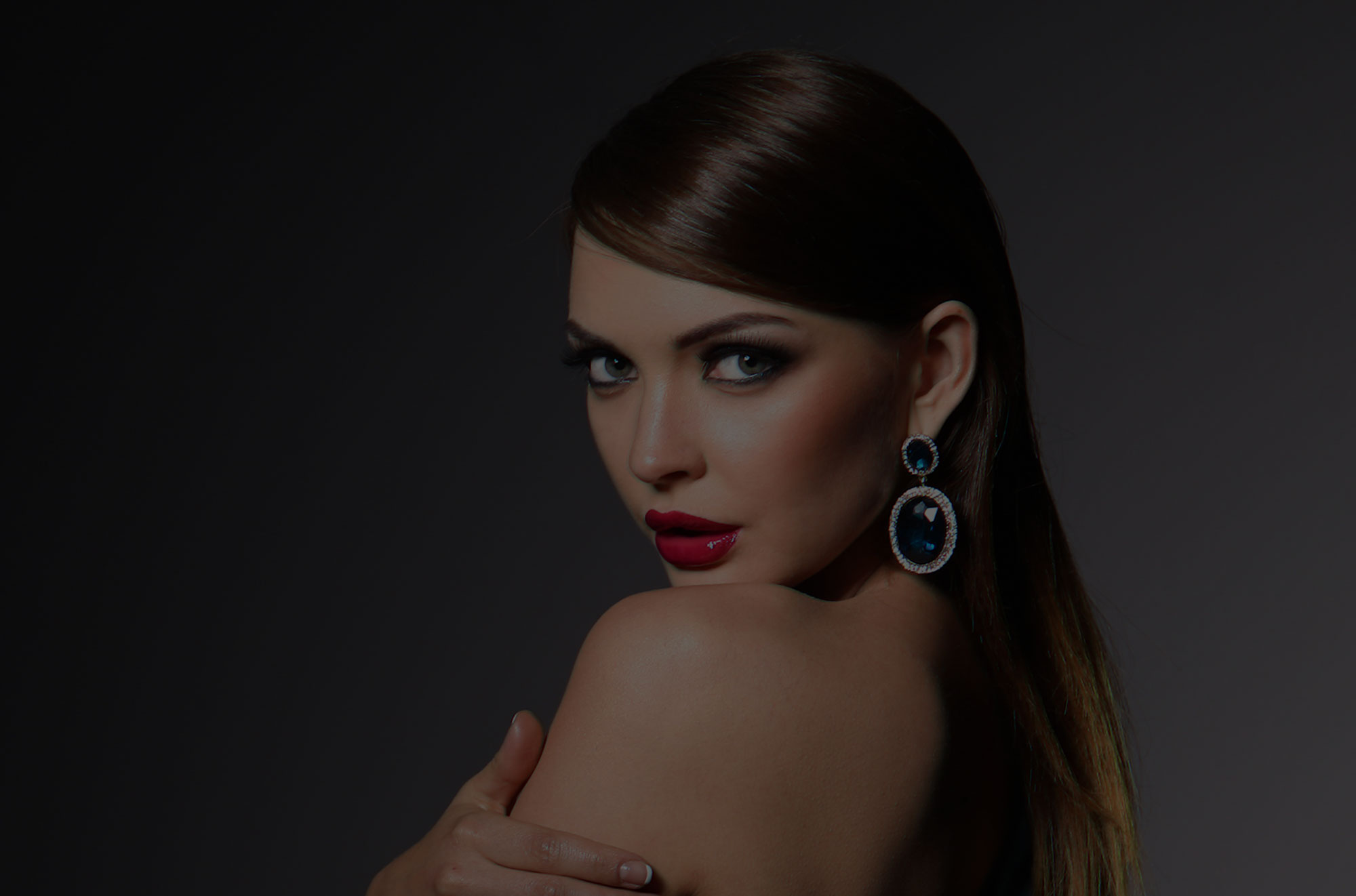Beautiful woman wearing hair up and sapphire earring looking over her bare shoulder.