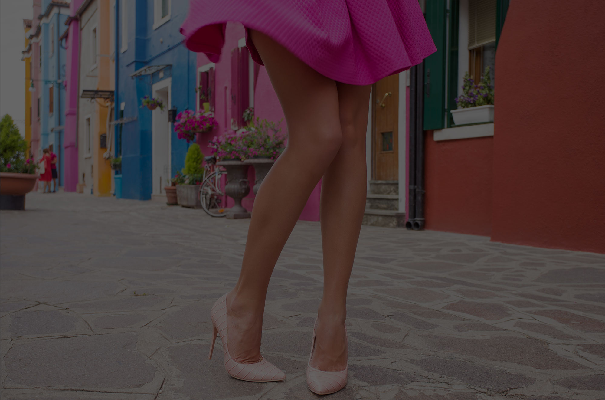 Woman wearing pink dress and high heels on village street.