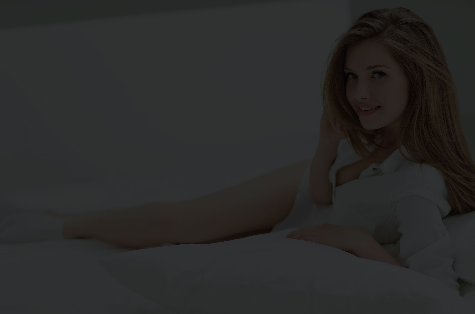Woman with long hair lying on side in bed.